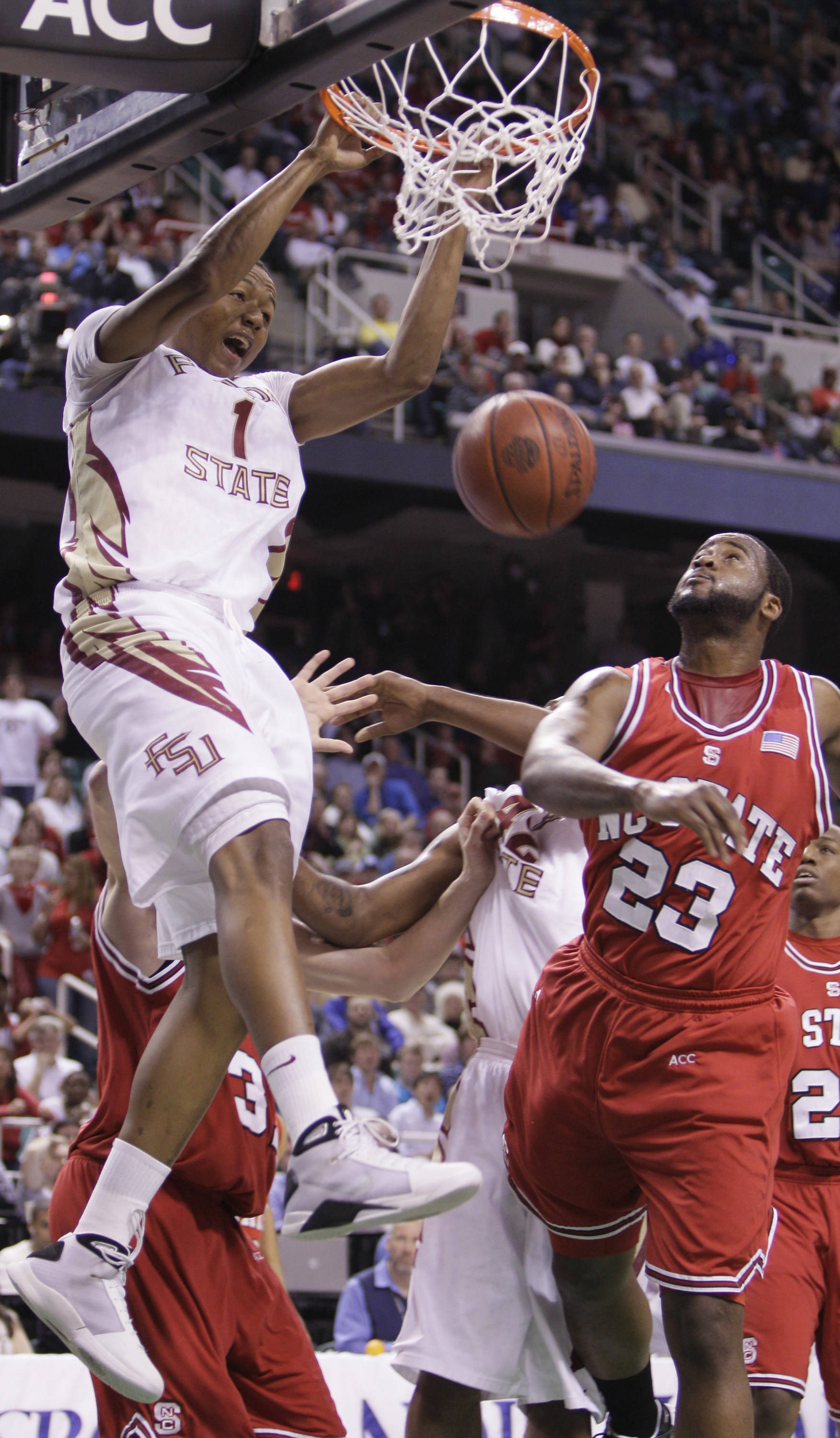 Florida State's Xavier Gibson (1) dunks the ball as North Carolina State's Tracy Smith (23) looks on during the first half of an NCAA college basketball game in the Atlantic Coast Conference tournament in Greensboro, N.C., Friday, March 12, 2010. (AP Photo/Gerry Broome)