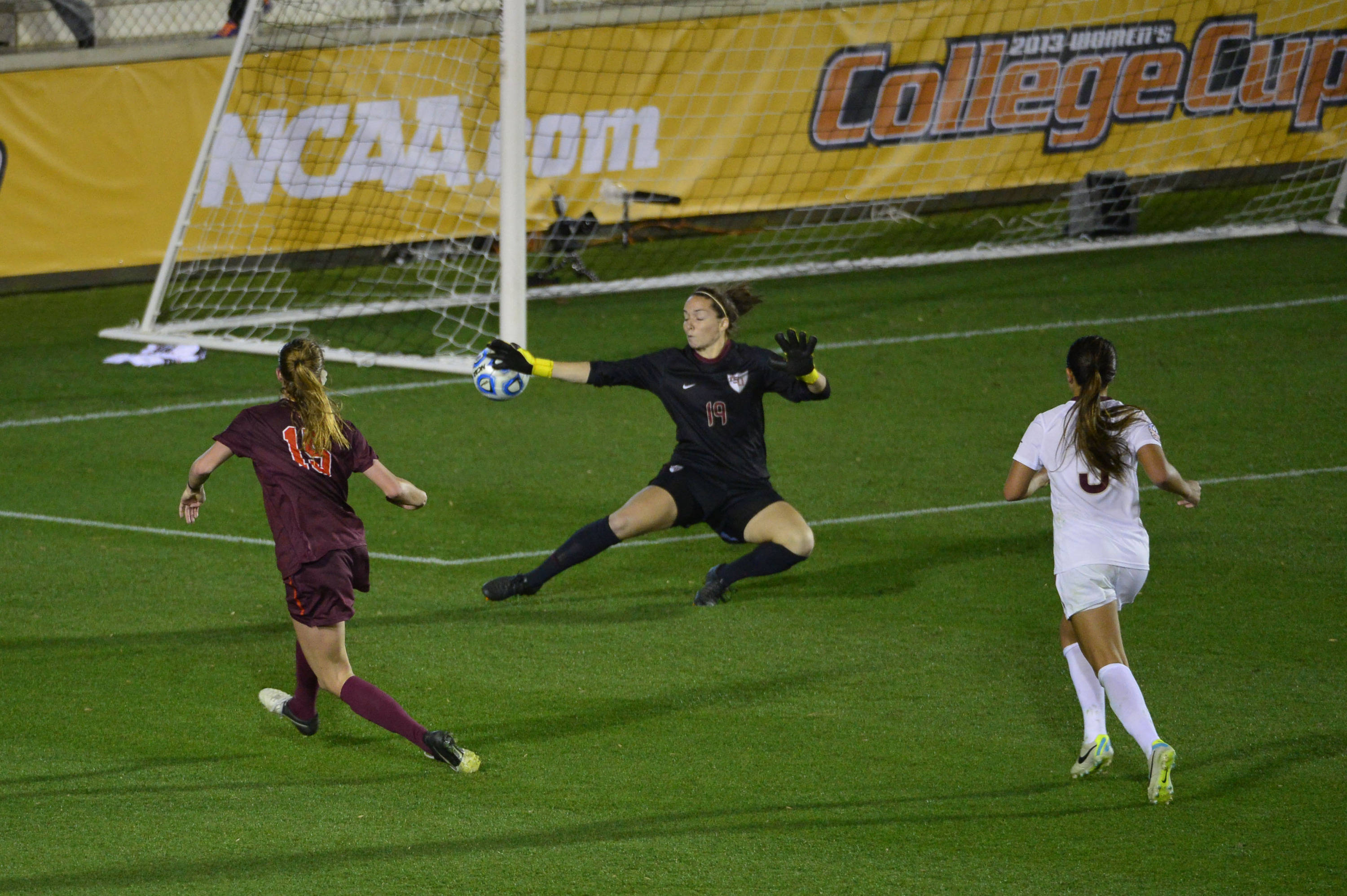 Dec 6, 2013; Cary, NC, USA; Virginia Tech Hokies midfielder Ashley Meier (15) scores a goal as Florida State Seminoles goalkeeper Kelsey Wys (19) and forward Nickolette Driesse (3) defend in the second half. The Seminoles defeated the Hokies 3-2 at WakeMed Soccer Park. Mandatory Credit: Bob Donnan-USA TODAY Sports