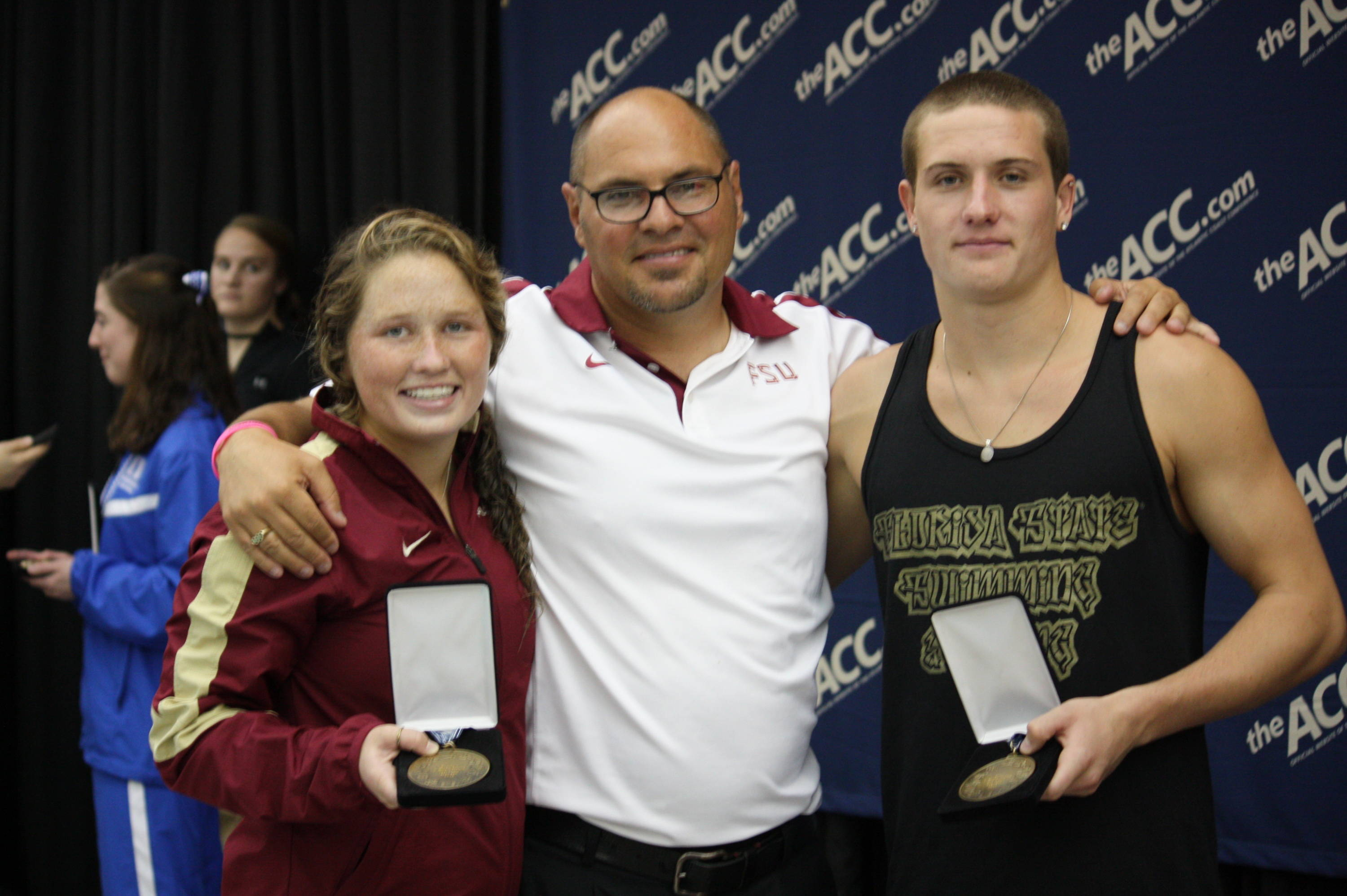 Head Coach Pat Jeffrey smiles with his bronze medalists, Kelsey Goodman and Tom Neubacher.