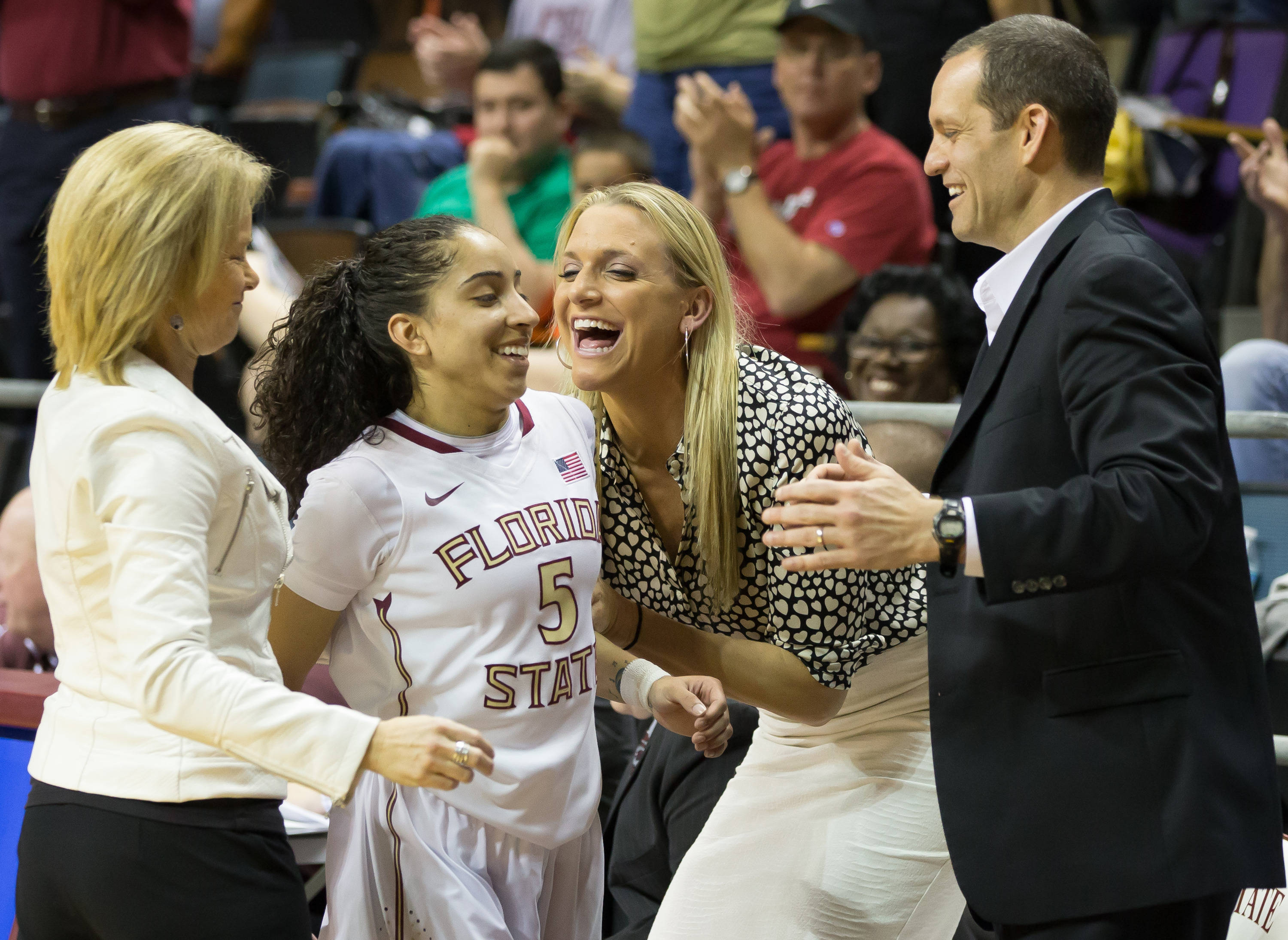Cheetah Delgado (5) is greeted by the coaching staff as she comes off the court in the final minutes.