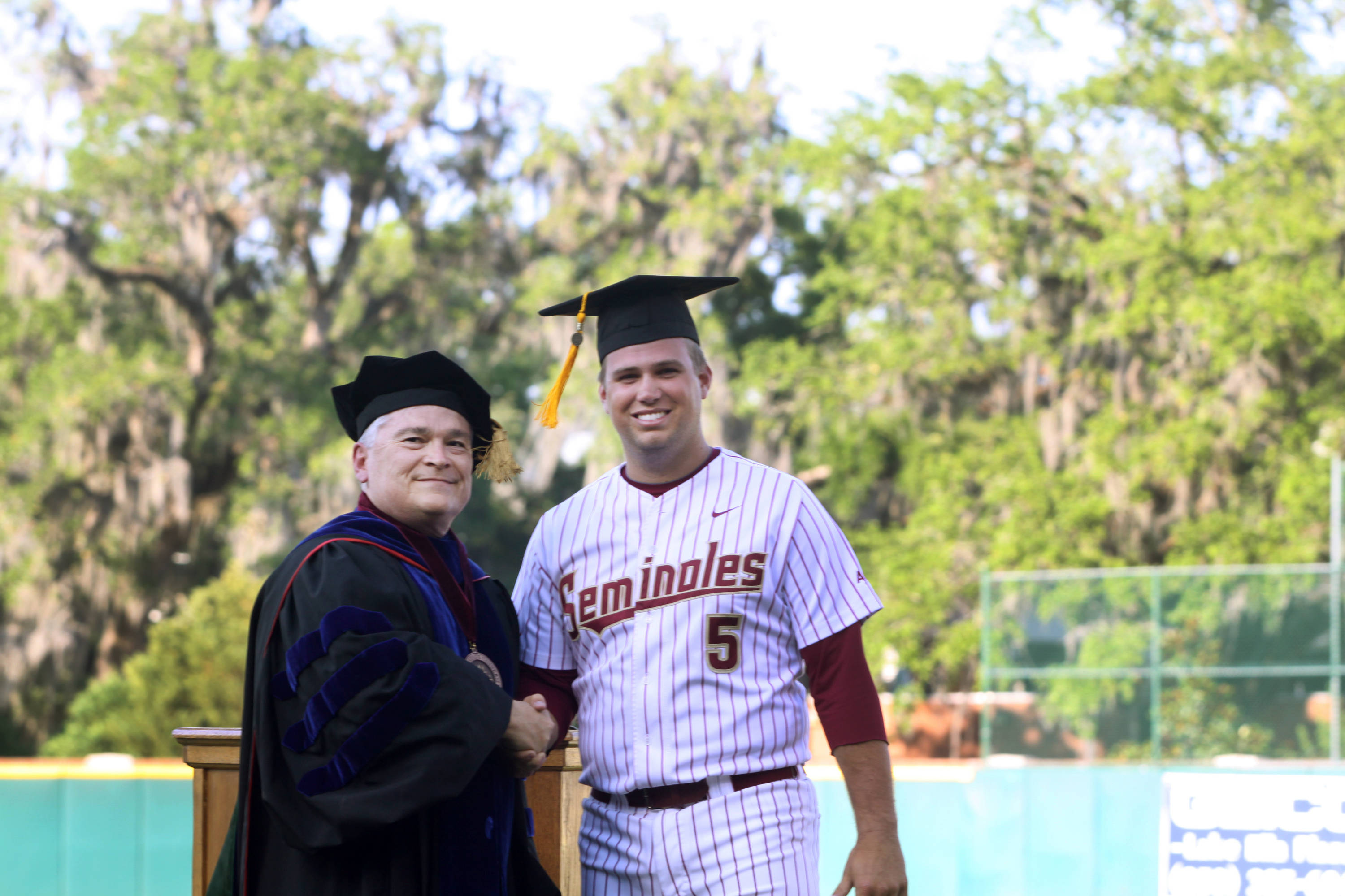 2011 Spring Graduation Ceremony held at Dick Howser Stadium to honor the graduating baseball seniors. Jack Posey (5) with President Barron
