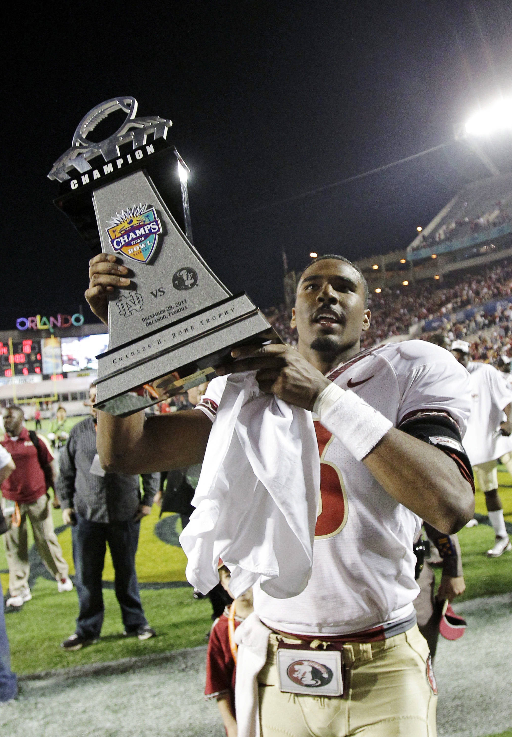 Florida State quarterback EJ Manuel carries the championship trophy off the field after defeating Notre Dame 18-14 in the Champs Sports Bowl. (AP Photo/John Raoux)