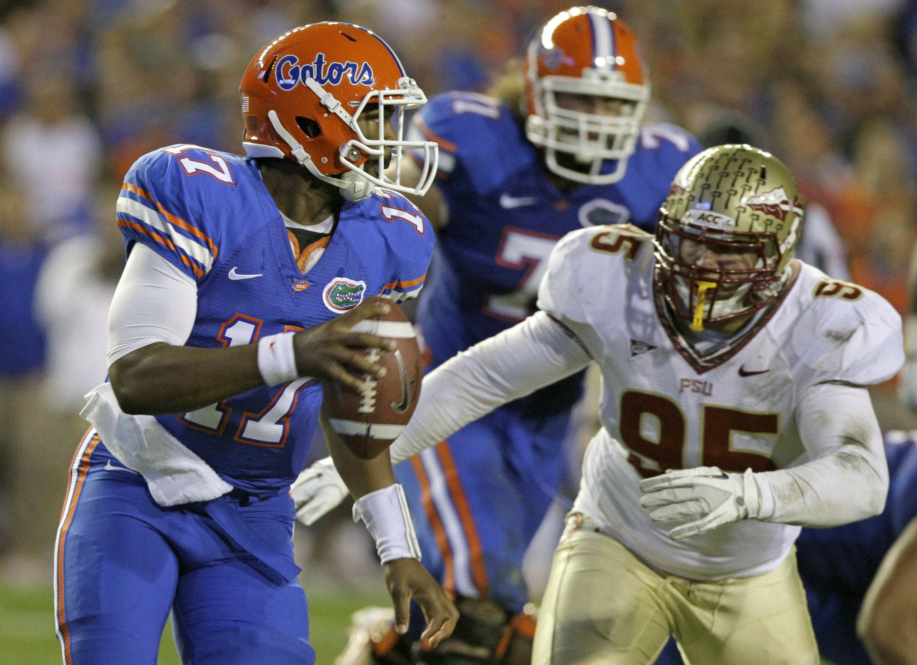 Florida quarterback Jacoby Brissett, left, scrambles as he looks for a receiver while Florida State defensive end Bjoern Werner (95) gives chase during the first half of an NCAA college football game on Saturday, Nov. 26, 2011, in Gainesville, Fla. (AP Photo/John Raoux)