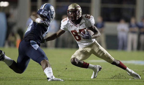 Florida State's Bert Reed (83) looks for some running room as North Carolina's Charles Brown (12) defends during the first half.
