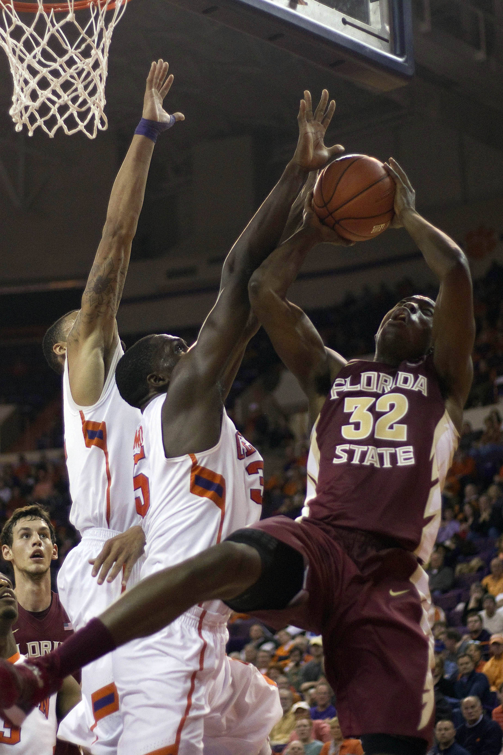 Jan 9, 2014; Clemson, SC, USA; Florida State Seminoles guard Montay Brandon (32) goes in for the layup while being defended by Clemson Tigers center Landry Nnoko (35) and forward K.J. McDaniels (32) during the second half at J.C. Littlejohn Coliseum. Seminoles won 56-41. Mandatory Credit: Joshua S. Kelly-USA TODAY Sports