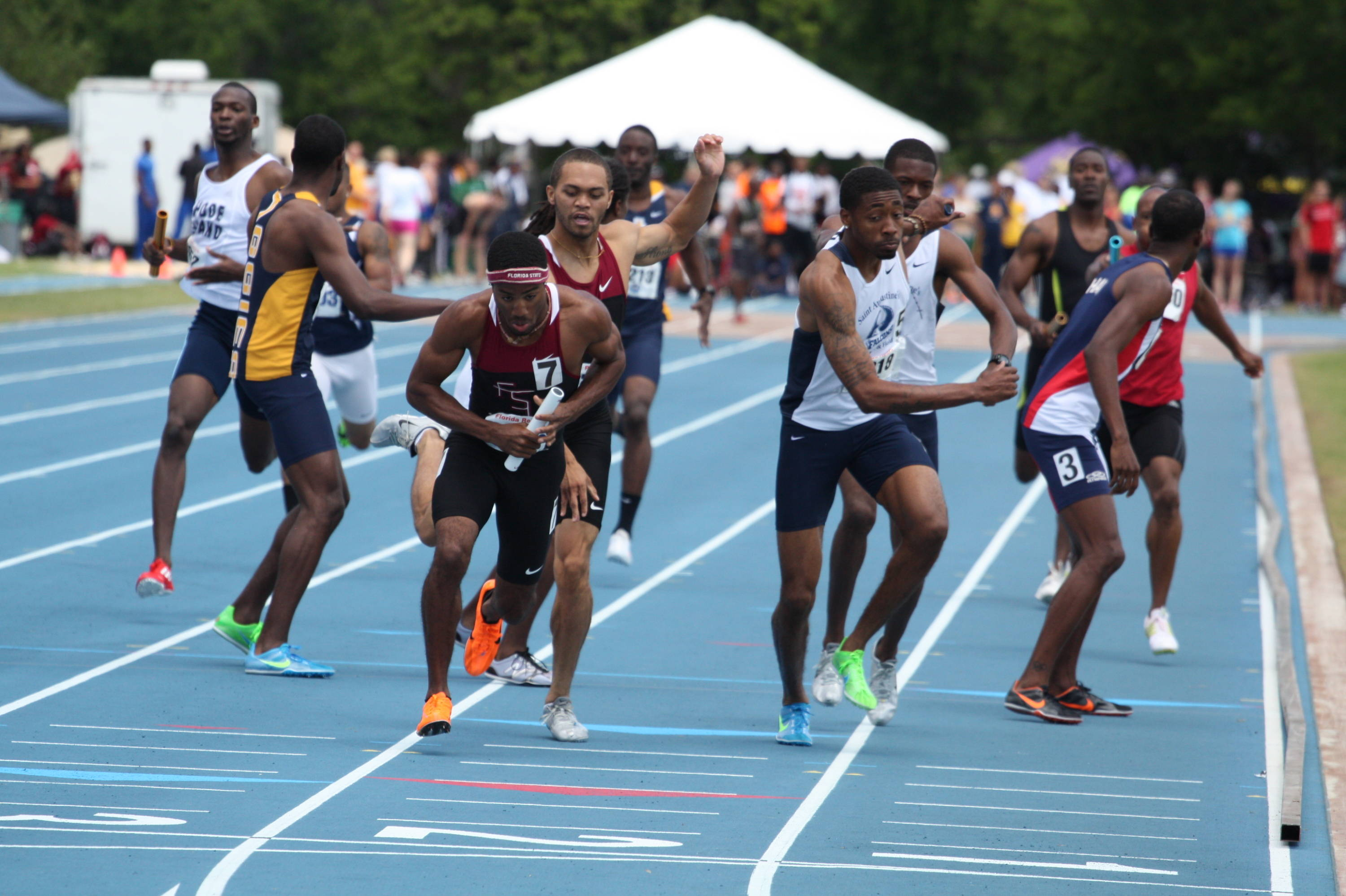 Darrin Gibson takes the baton from Ronald Bolden and prepares to cut inside after the final exchange in the sprint medley.