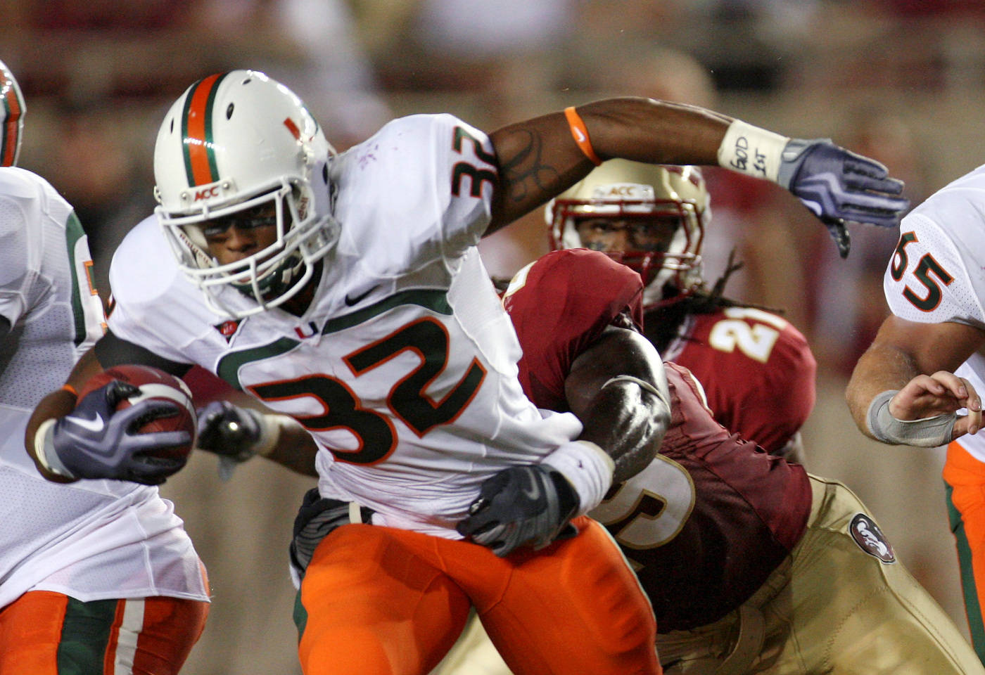 Miami running back Lee Chambers, left, tries to get away from Florida State linebacker Kendall Smith during the second quarter of an NCAA college football game Monday, Sept. 7, 2009, in Tallahassee, Fla.(AP Photo/Phil Coale)