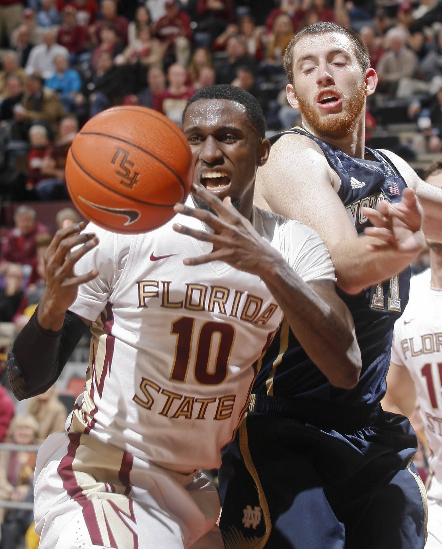 Jan 21, 2014; Tallahassee, FL, USA; Florida State Seminoles forward Okaro White (10) goes for a rebound as Notre Dame Fighting Irish center Garrick Sherman (11) is out of position in the second half at the Donald L. Tucker Center. The Florida State Seminoles beat the Notre Dame Fighting Irish 76-74. Mandatory Credit: Phil Sears-USA TODAY Sports