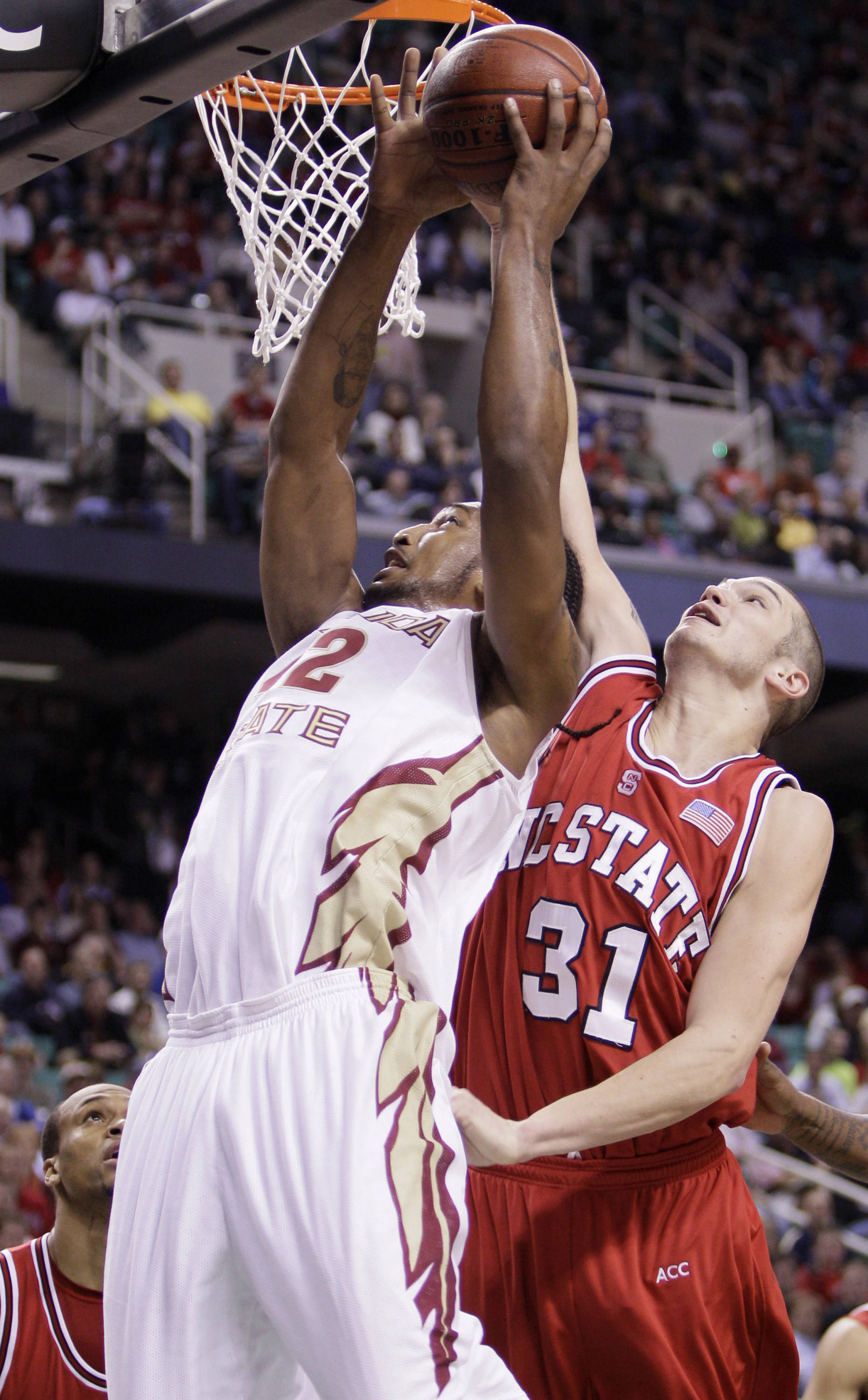 Florida State's Ryan Reid (42) heads to the rim as North Carolina State's Dennis Horner (31) during the first half of an NCAA college basketball game in the Atlantic Coast Conference tournament in Greensboro, N.C., Friday, March 12, 2010. (AP Photo/Gerry Broome)