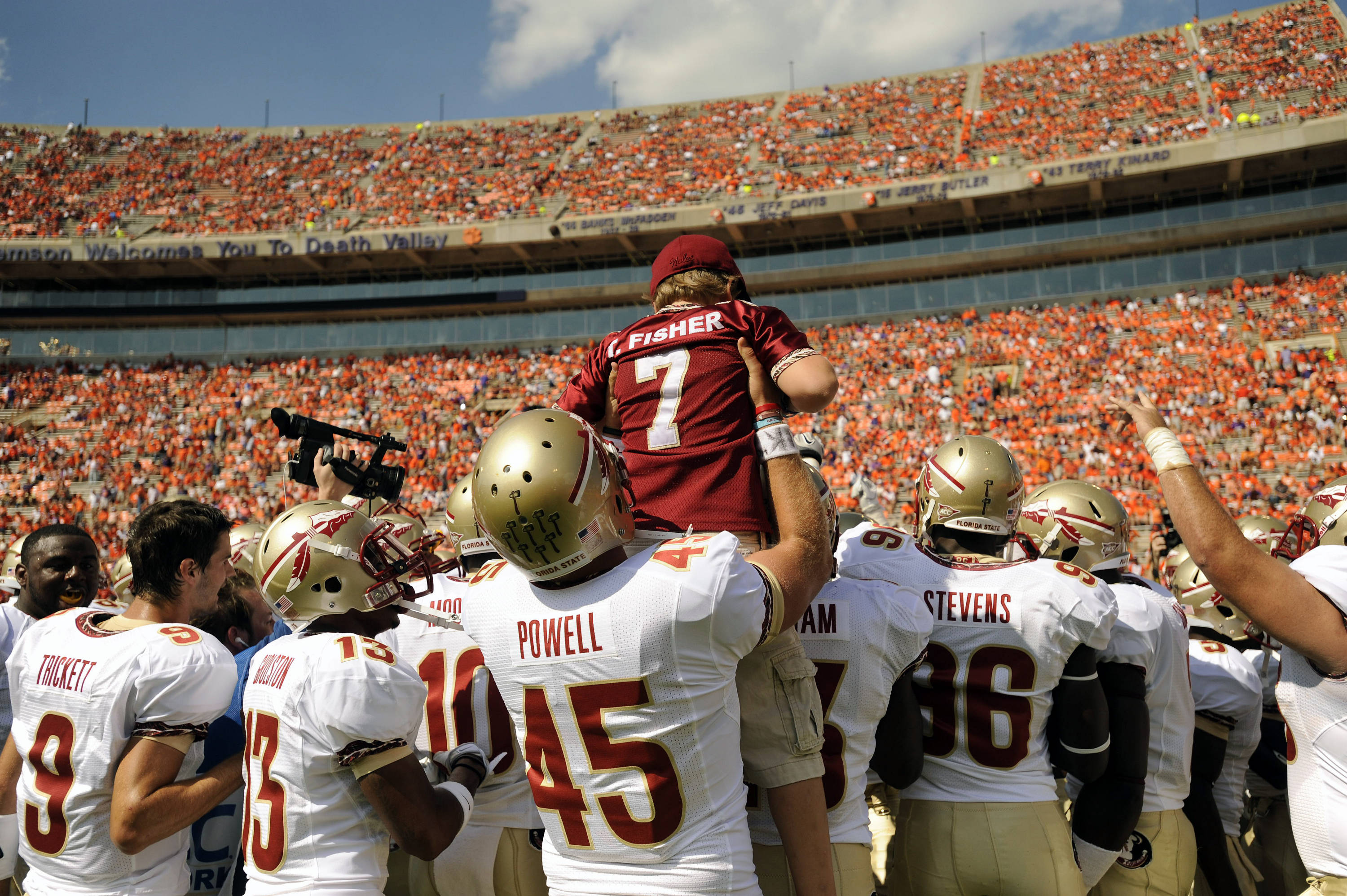 Shawn Powell holds up Trey Fisher during a team huddle.