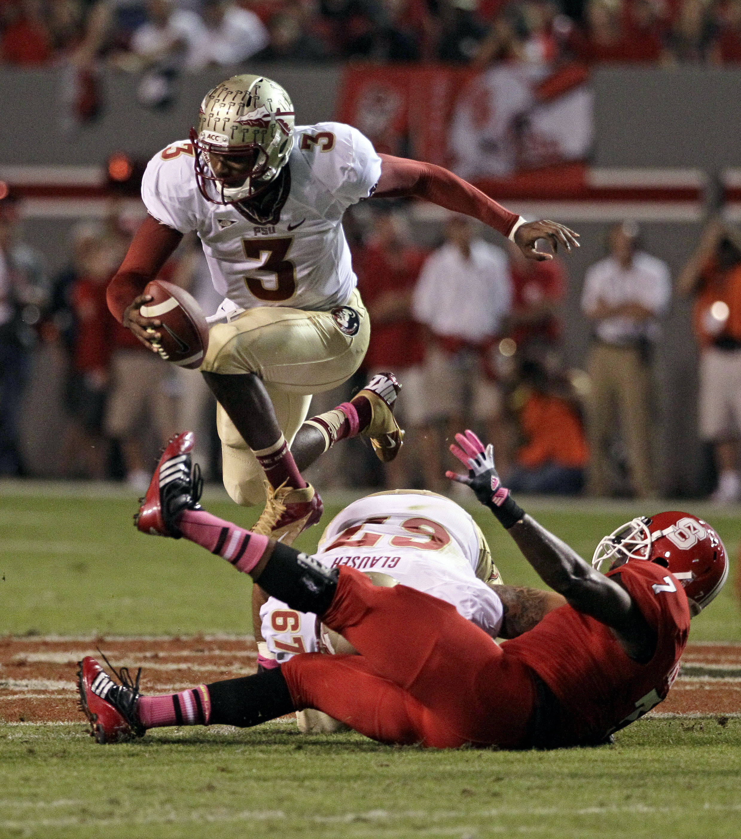 Florida State quarterback EJ Manuel (3) jumps over North Carolina State's Sterling Lucas (7). (AP Photo/Gerry Broome)