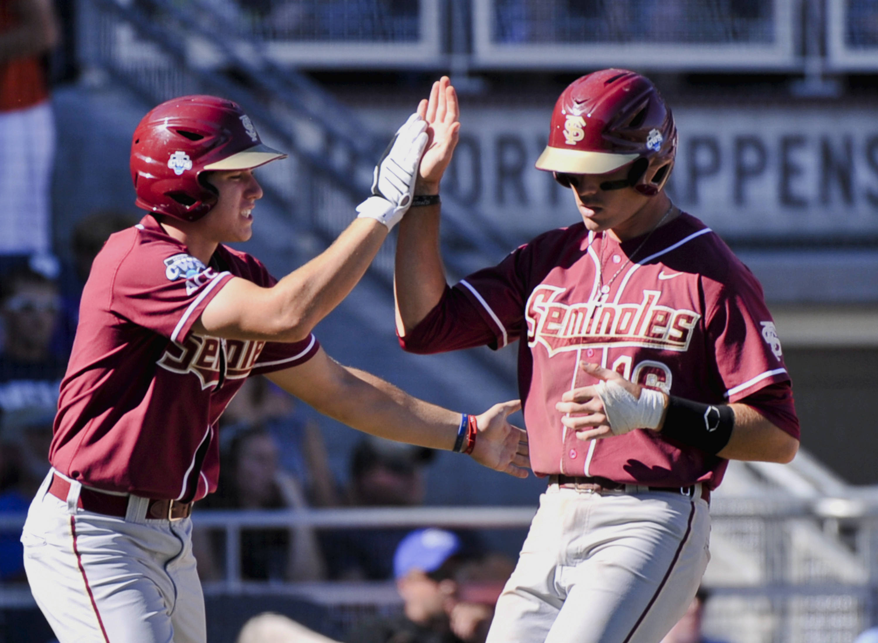 Florida State's Jayce Boyd, right, is greeted by teammate Josh Delph after Boyd scored against Arizona on a double hit by Justin Gonzalez in the fourth inning. (AP Photo/Ted Kirk)