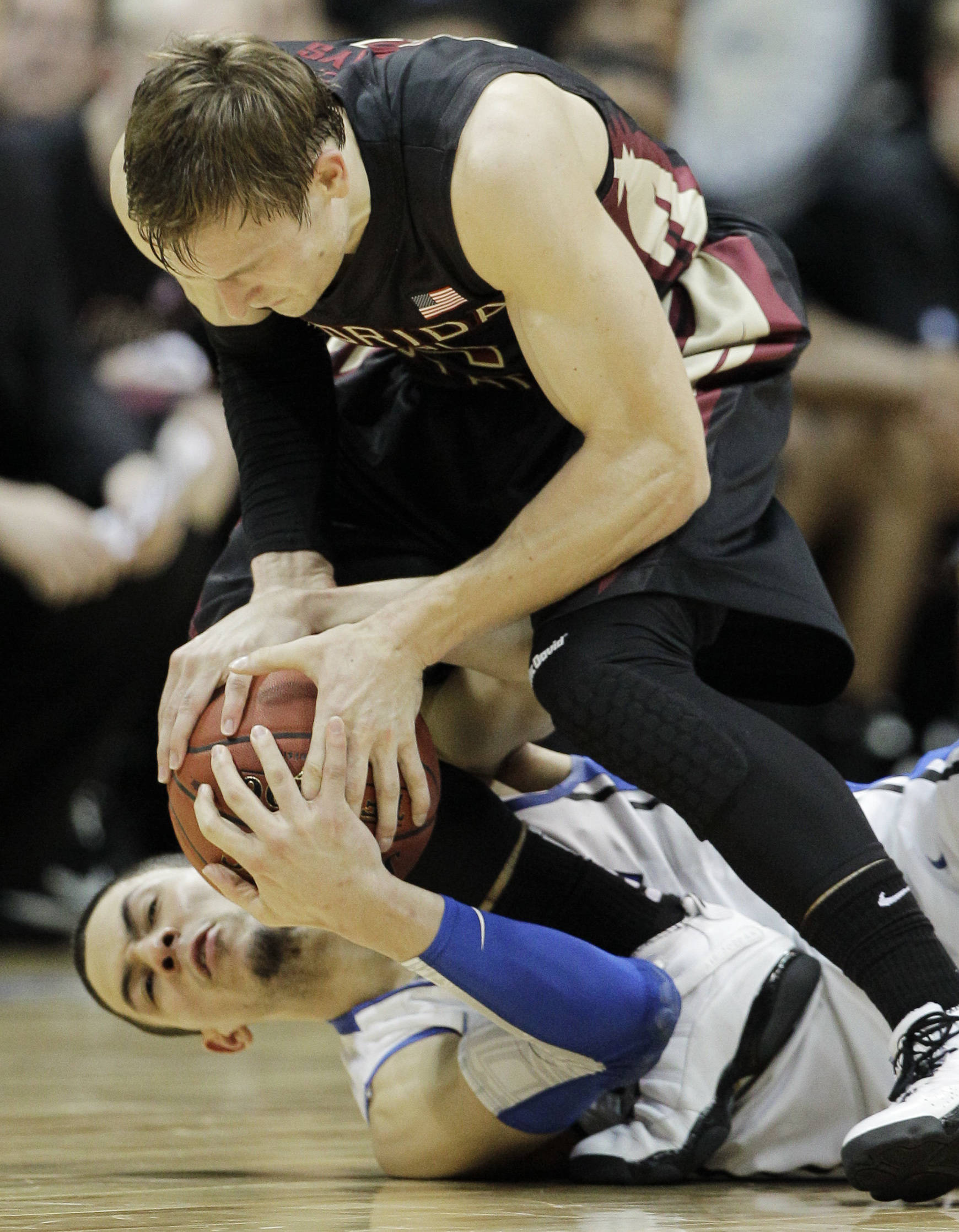 Duke guard Austin Rivers, bottom, and Florida State guard Deividas Dulkys (4) grab for a lose ball during the second half of an NCAA college basketball game in the semifinals of the Atlantic Coast Conference tournament, Saturday, March 10, 2012, in Atlanta. (AP Photo/Chuck Burton)