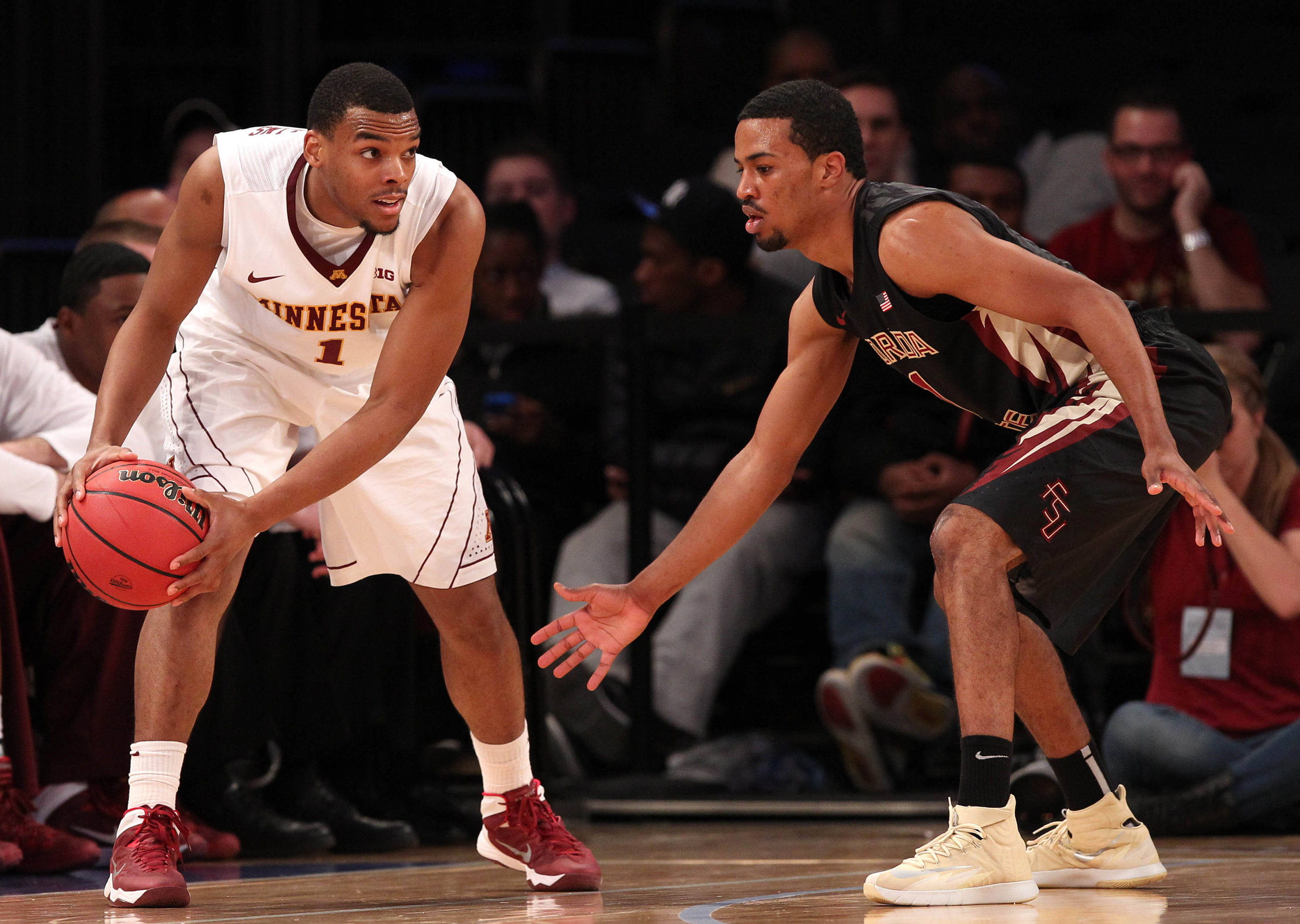 Apr 1, 2014; New York, NY, USA; Minnesota Golden Gophers guard Andre Hollins (1) looks to pass defended by Florida State Seminoles guard Devon Bookert (1) during the second half at Madison Square Garden. The Minnesota Golden Gophers defeated the Florida State Seminoles 67-64 in overtime. Mandatory Credit: Adam Hunger-USA TODAY Sports
