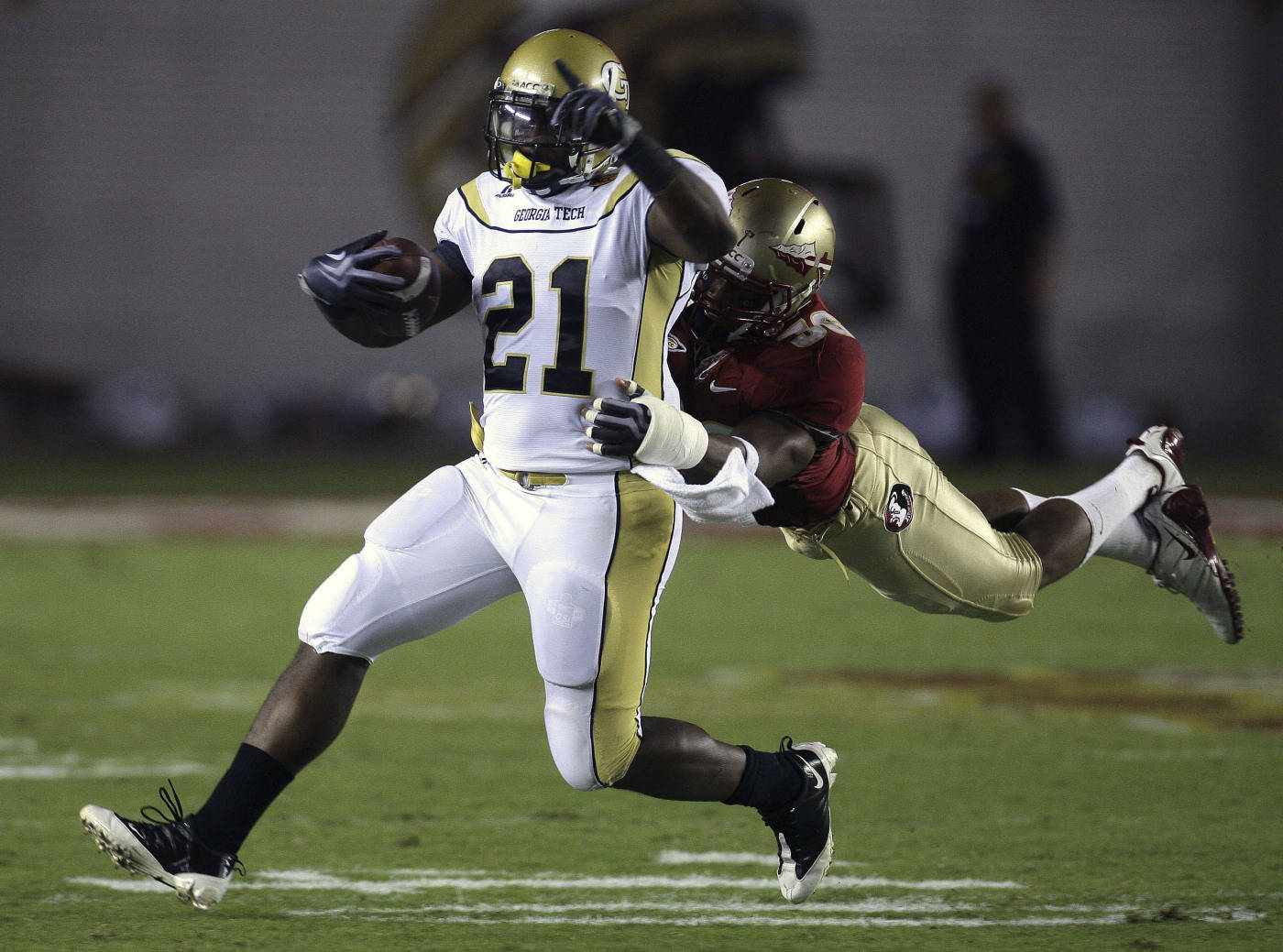 Georgia Tech running back Jonathan Dwyer, left, runs for first-quarter yardage as Florida State linebacker Dekoda Watson tries to make the stop during an NCAA college football game, Saturday, Oct. 10, 2009, in Tallahassee, Fla.