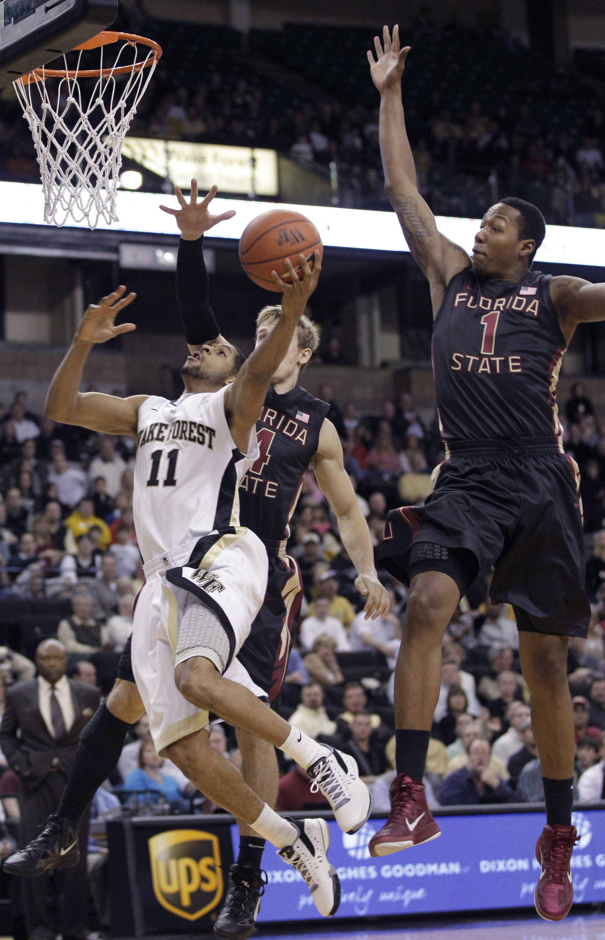 Wake Forest's C.J. Harris (11) drives past Florida State's Xavier Gibson and Deividas Dulkys. (AP Photo/Chuck Burton)