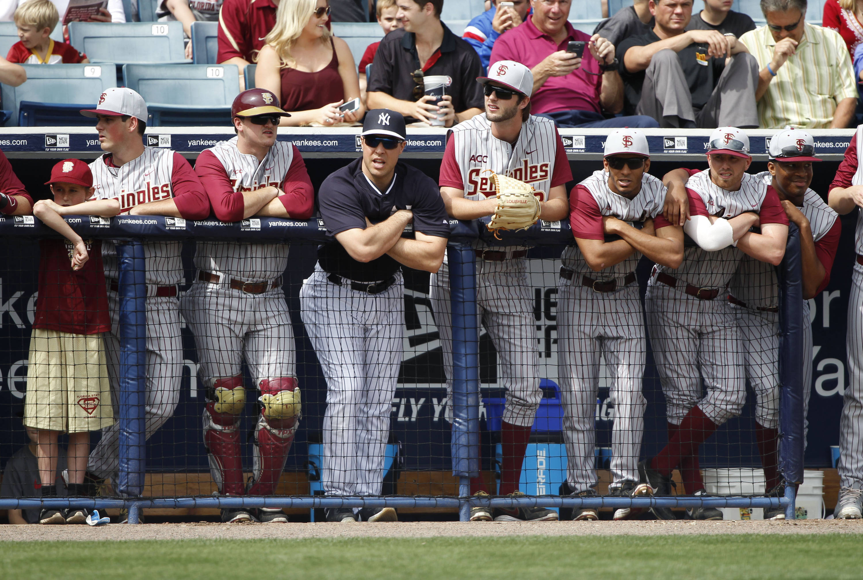 Feb 25, 2014; Tampa, FL, USA; New York Yankees first baseman Mark Teixeira (25) stands in the dugout with the  Florida State Seminoles players at George M. Steinbrenner Field. Mandatory Credit: Kim Klement-USA TODAY Sports
