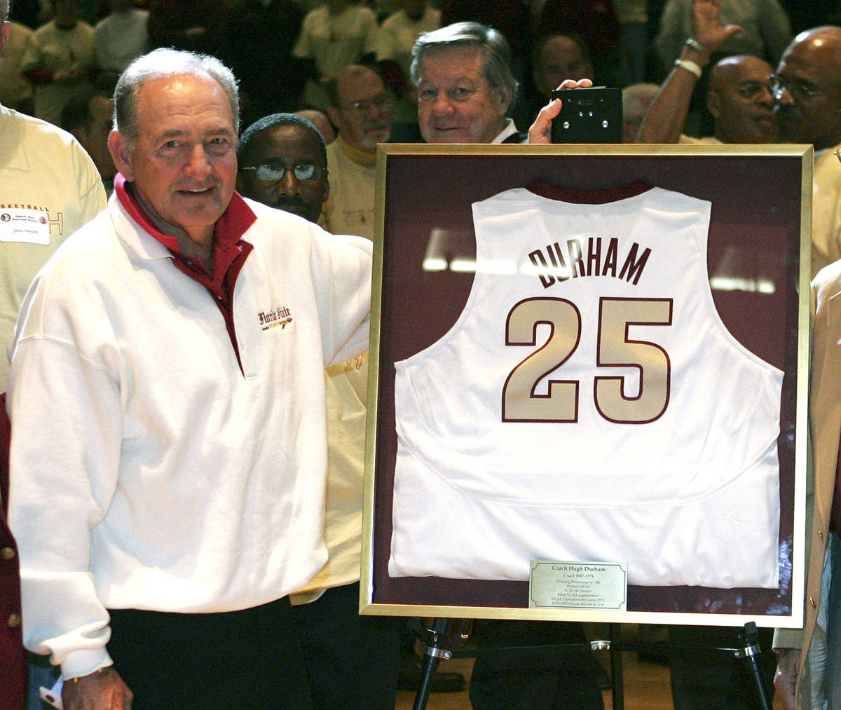 Hugh Durham, left, former head coach and player at Florida State University, left, poses with his retired jersey during half-time ceremonies honoring Durham and the 1972 FSU team during a college basketball game against Miami, Saturday, Jan. 20, 2007, in Tallahassee, Fla. (AP Photo/Brandon Goodman)