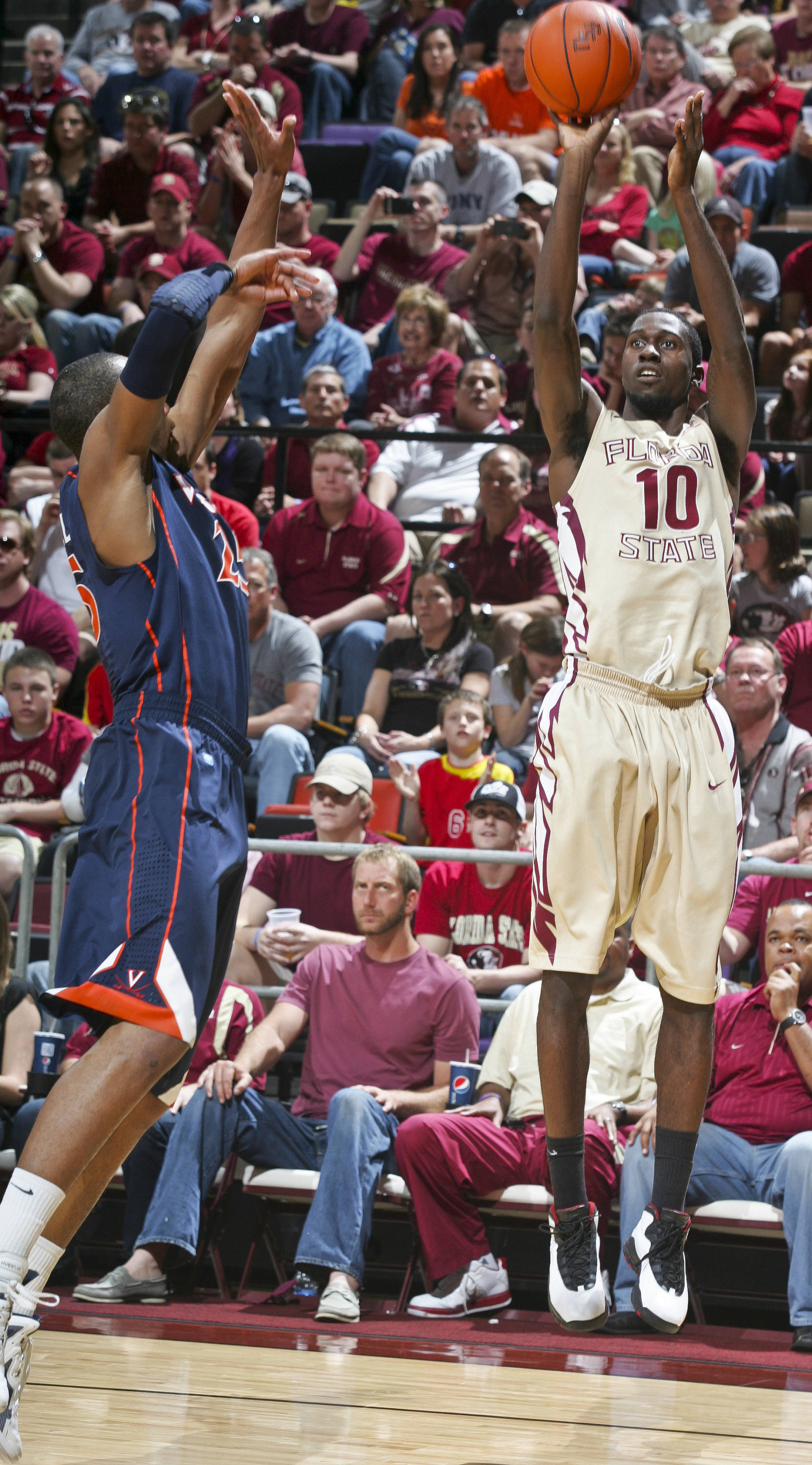Florida State's Okaro White (10) shoots from the corner over Virginia's Akil Mitchell (25) in the first half of an NCAA college basketball game on Saturday, Feb. 4, 2012, in Tallahassee, Fla. Florida State won 58-55. (AP Photo/Phil Sears)