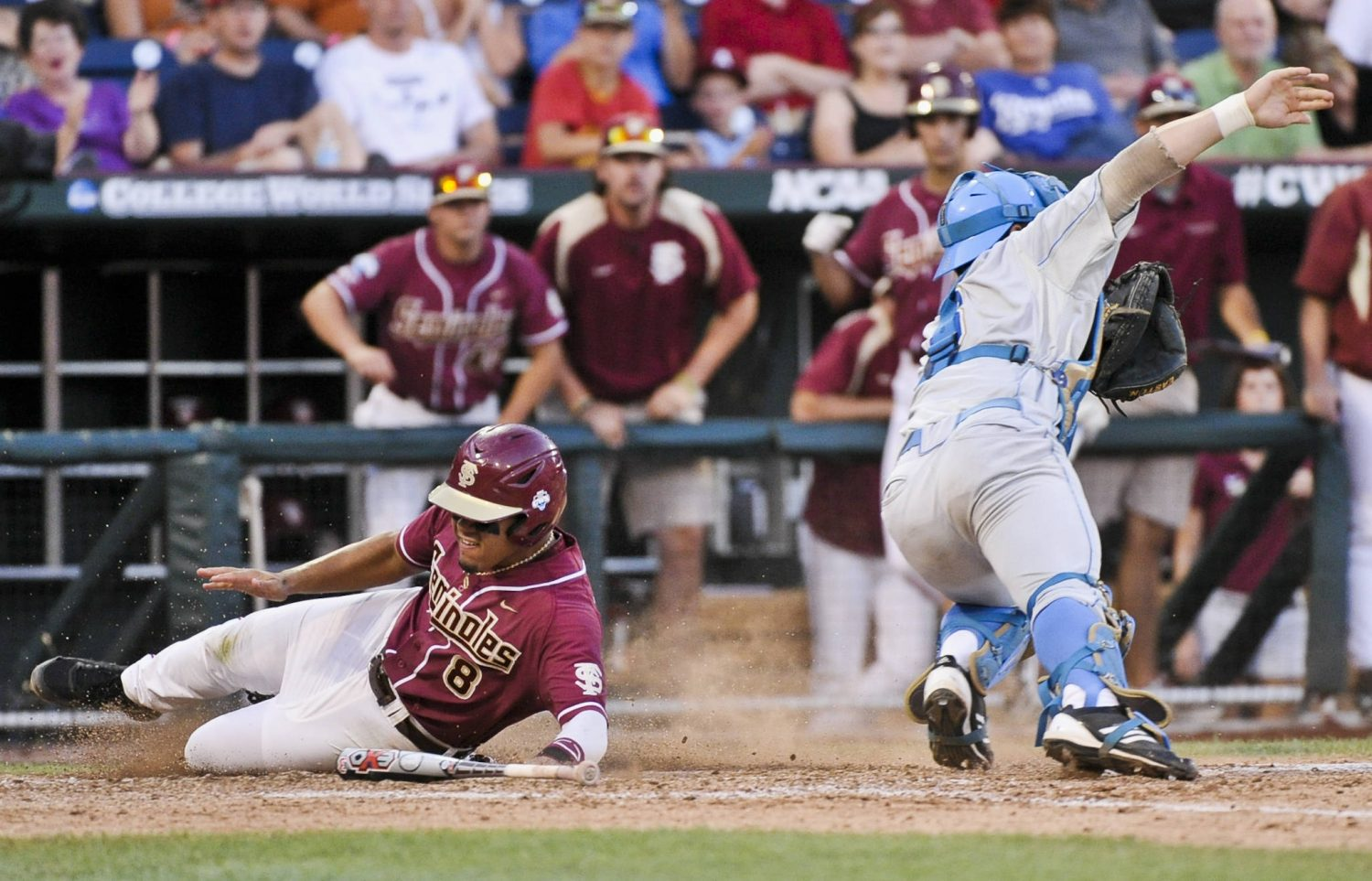 Florida State's Devon Travis, left, scores at home plate against UCLA catcher Tyler Heineman on a throwing error of third baseman Kevin Kramer, in the fourth inning. Florida State's Steven Rodriguez also scored on the play. (AP Photo/Ted Kirk)
