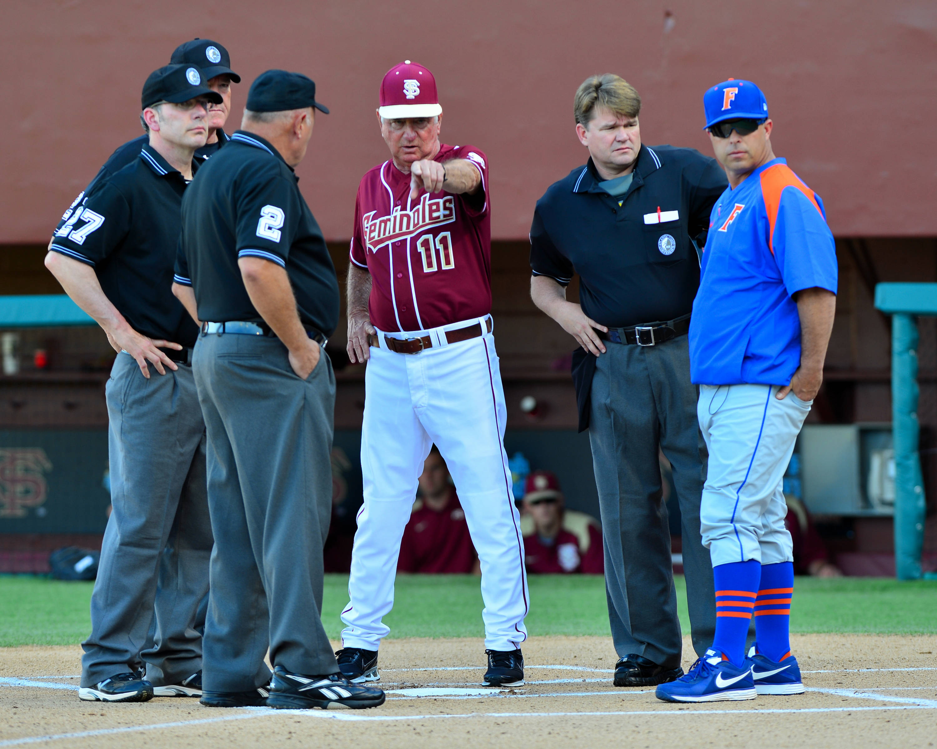 FSU head coach Mike Martin and UF head coach Kevin O'Sullivan meet with the umpires before Tuesday night's game.