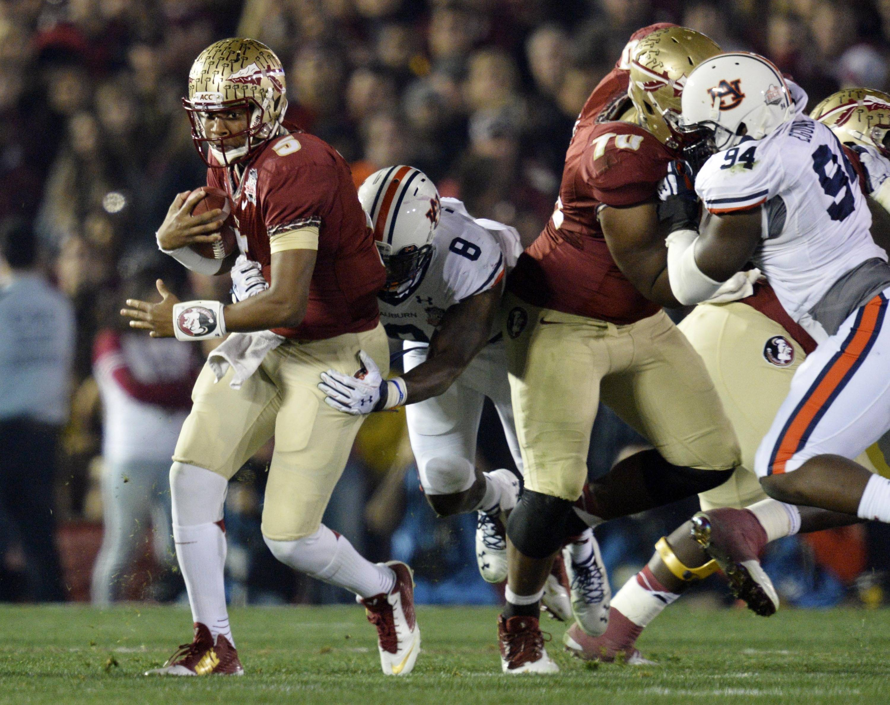 Jan 6, 2014; Pasadena, CA, USA; Florida State Seminoles quarterback Jameis Winston (5) is tackled by Auburn Tigers linebacker Cassanova McKinzy (8) during the first half of the 2014 BCS National Championship game at the Rose Bowl.  Mandatory Credit: Robert Hanashiro-USA TODAY Sports