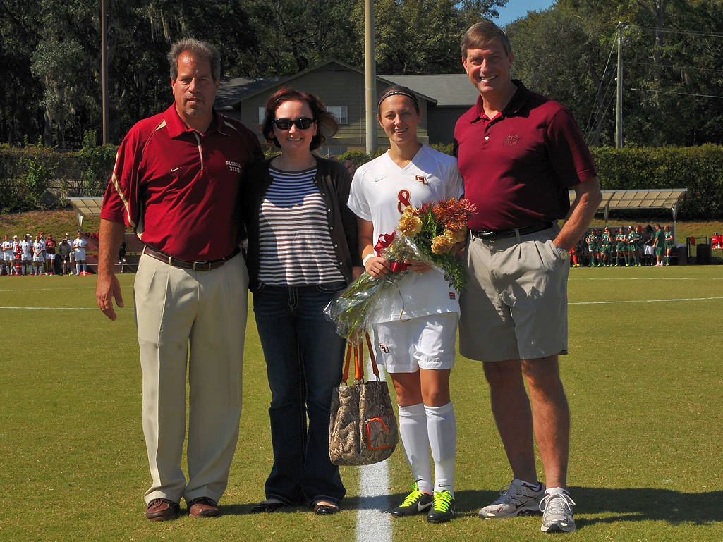 Head coach Mark Krikorian and Director of Athletics Randy Spetman with Katya Gokhman and her mom on senior day.