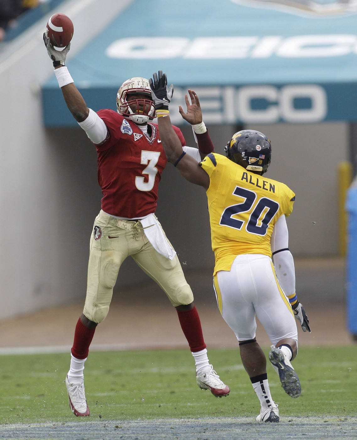 Florida State quarterback E.J. Manuel, left, throws a second-quarter pass as West Virginia defensive back Franchor Allen attempts to make the tackle during the Gator Bowl NCAA college football game, Friday, Jan. 1, 2010, in Jacksonville, Fla.(AP Photo/Phil Coale)