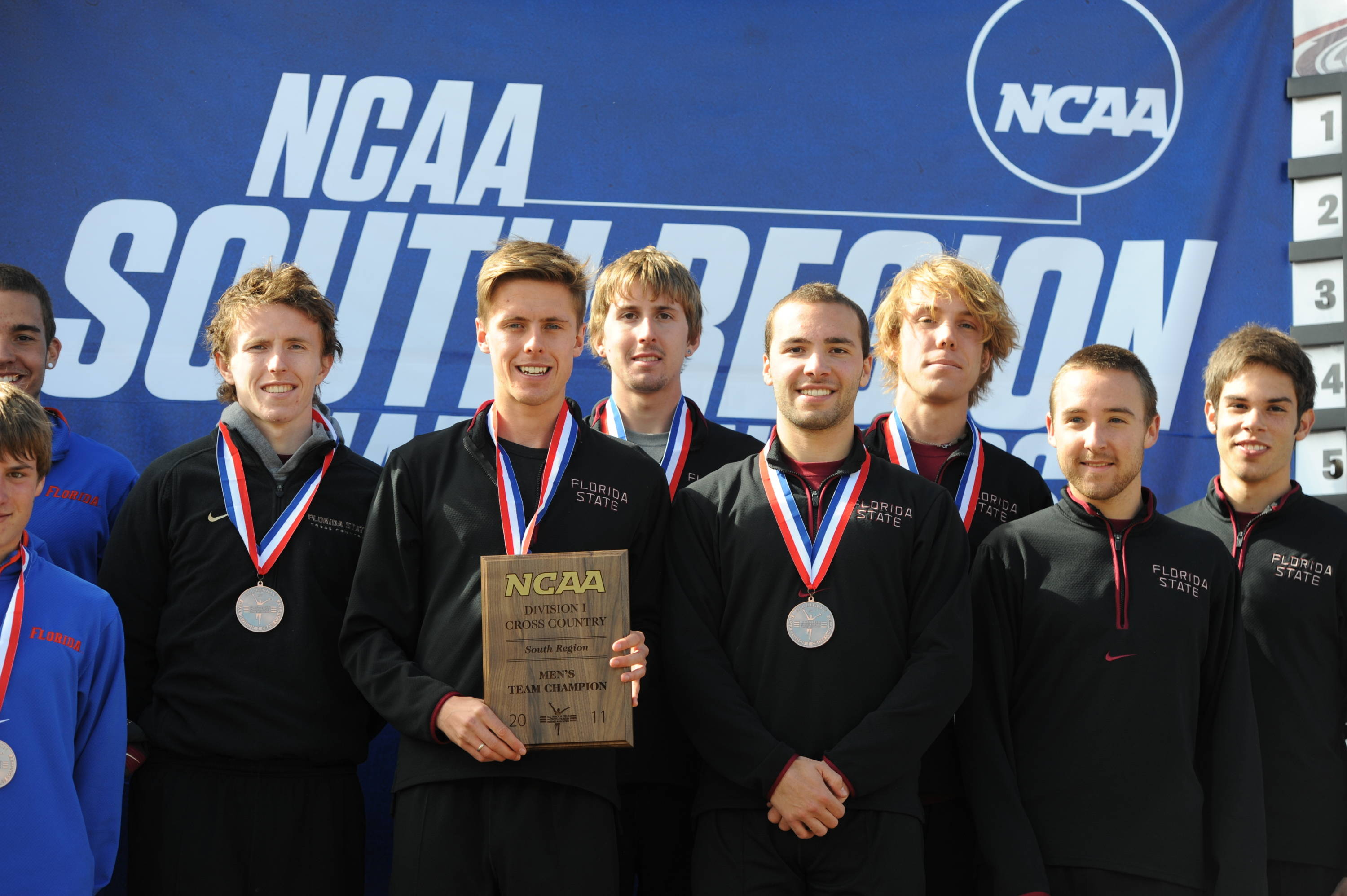 The Florida State men's cross country team poses on the podium after capturing the 2011 NCAA South Region title. It was the first for the men since 2006.