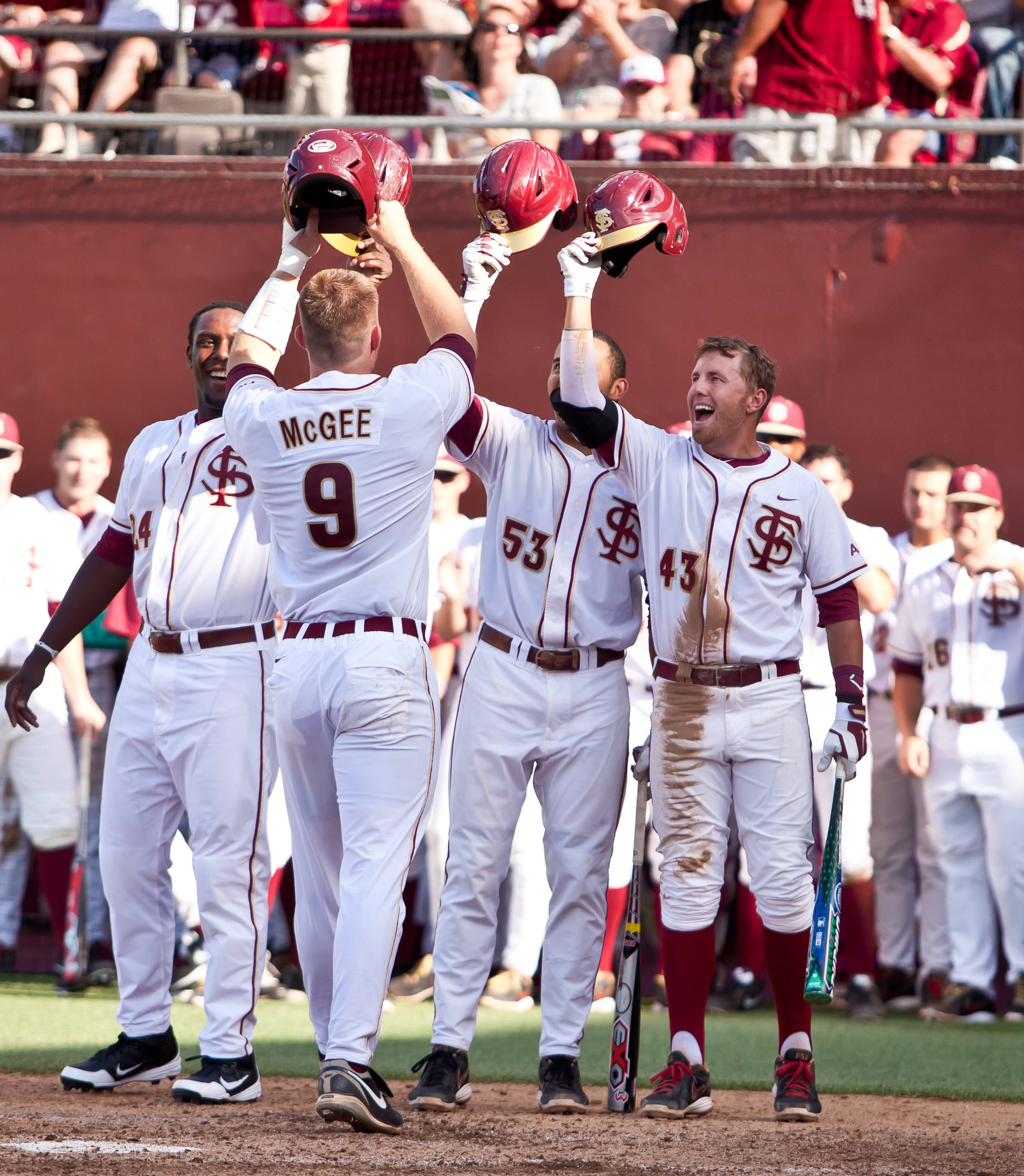 The Seminoles greet Stephen McGee at the plate after the Florida State catcher hit a two-run home run.