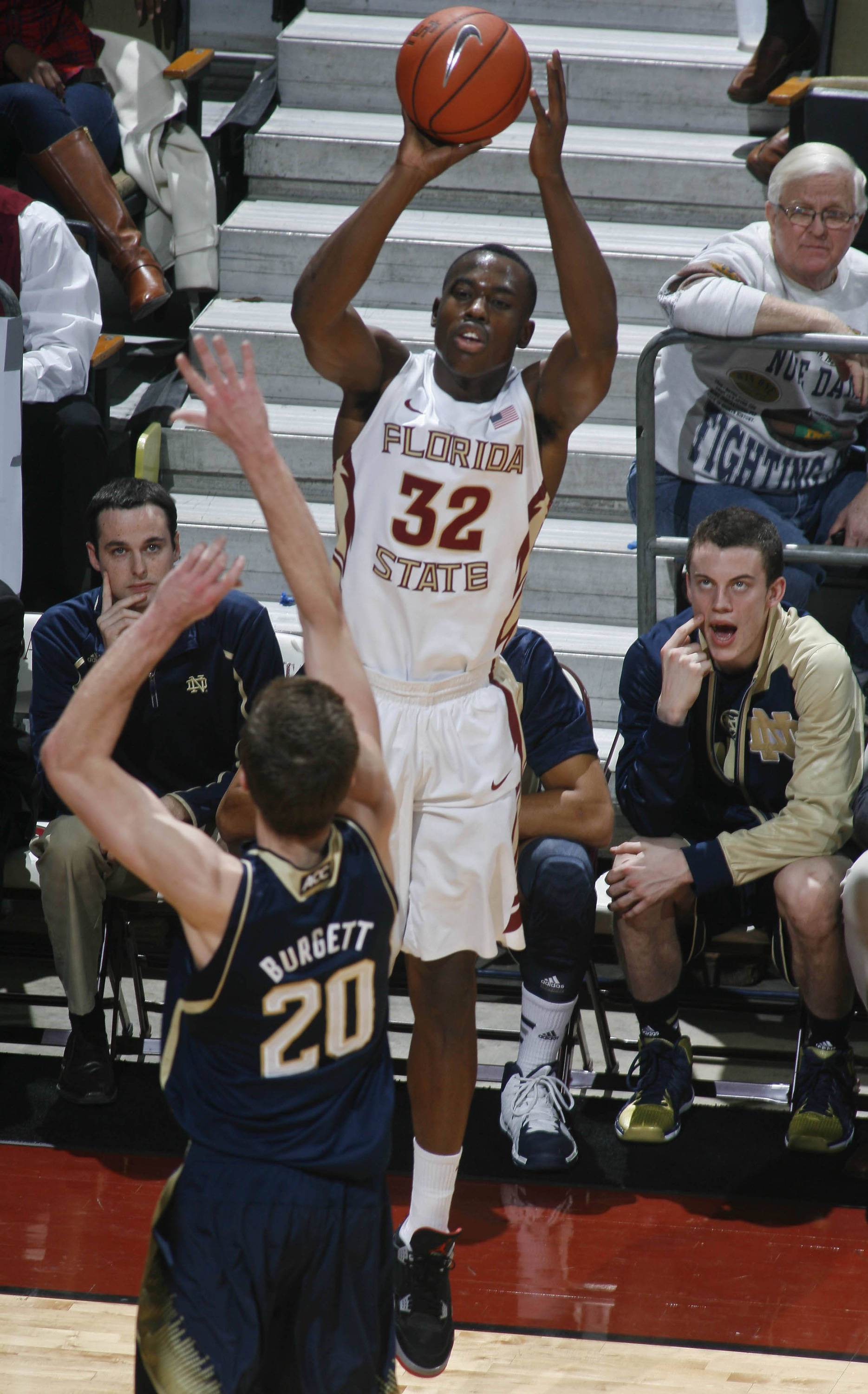 Jan 21, 2014; Tallahassee, FL, USA; Florida State Seminoles guard Montay Brandon (32) makes a three-point shot as Notre Dame Fighting Irish forward Austin Burgett (20) defends in the first half at the Donald L. Tucker Center. Mandatory Credit: Phil Sears-USA TODAY Sports