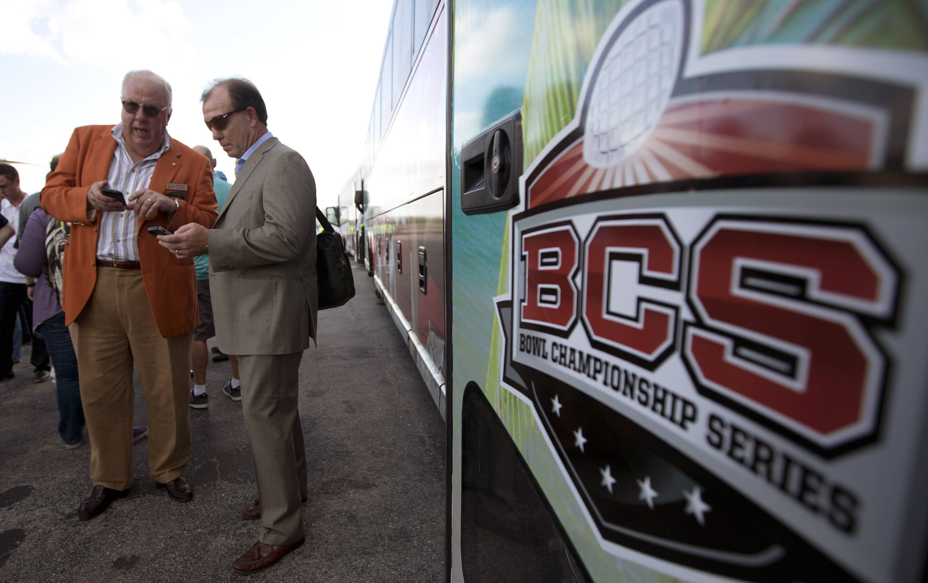 An Orange Bowl official, left, talks to Florida State football coach Jimbo Fisher, Wednesday, Dec. 26, 2012, after his team arrived in Fort Lauderdale, Fla., for the Orange Bowl Classic NCAA college football game against Northern Illinois in Miami, Jan. 1, 2013. (AP Photo/J Pat Carter)