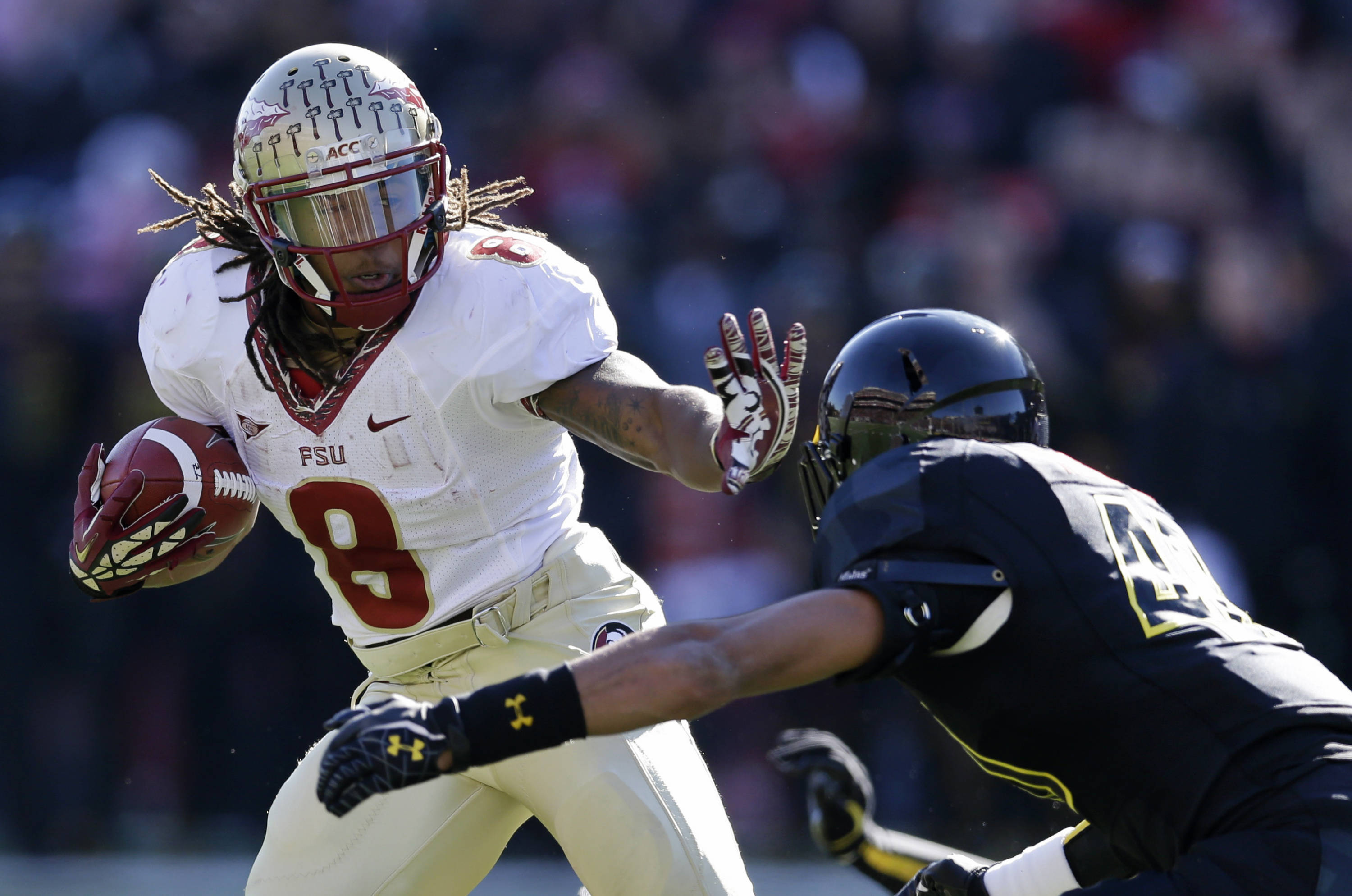 Tailback Devonta Freeman, left, rushes past Maryland defensive back Matt Robinson in the first half of an NCAA college football game in College Park, Md., Saturday, Nov. 17, 2012. (AP Photo/Patrick Semansky)
