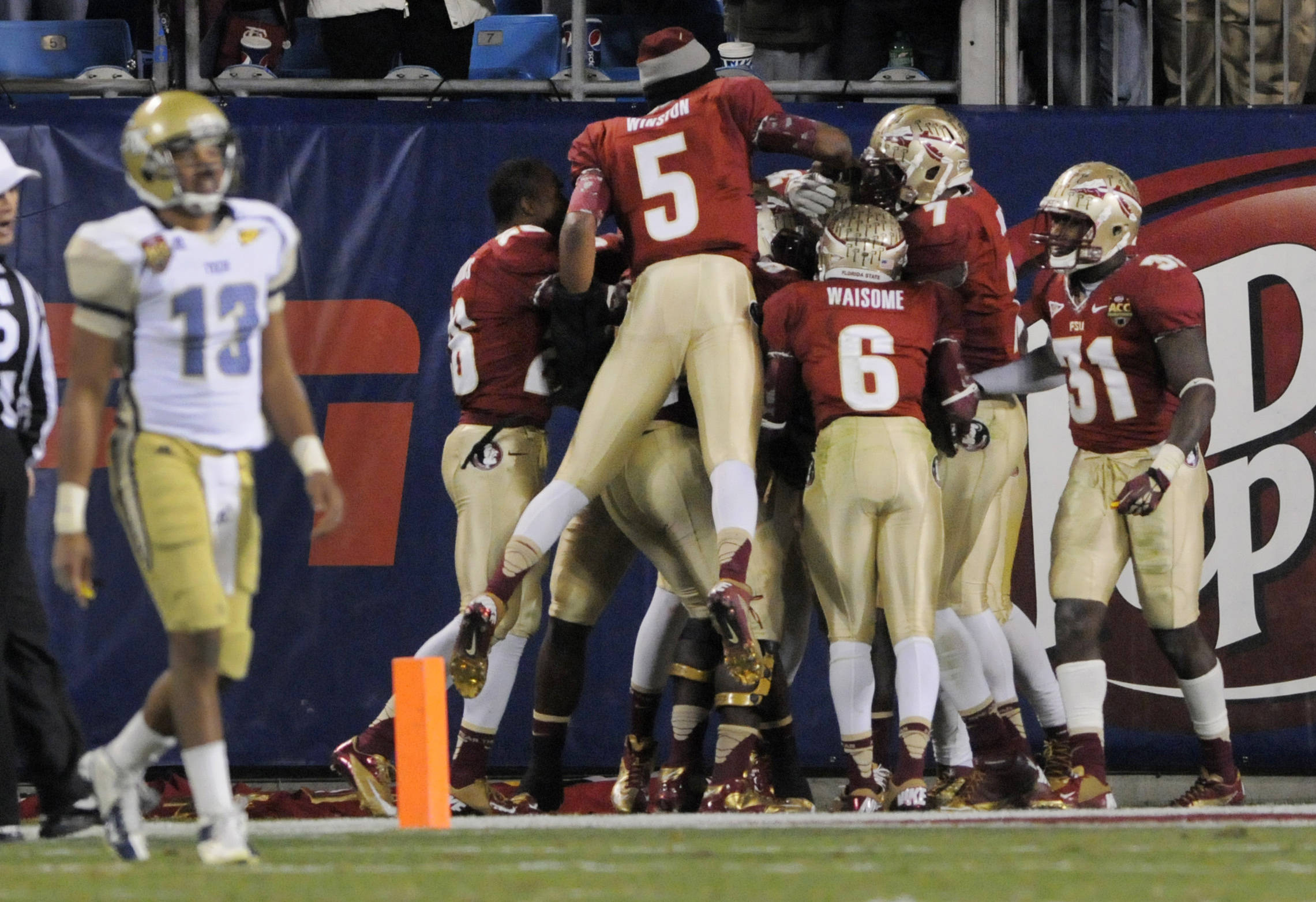 Georgia Tech's Tevin Washington (13) walks off the field as Florida State players celebrate an interception during the second half of the Atlantic Coast Conference championship NCAA college football game in Charlotte, N.C., Sunday, Dec. 2, 2012. Florida State won 21-15. (AP Photo/Mike McCarn)