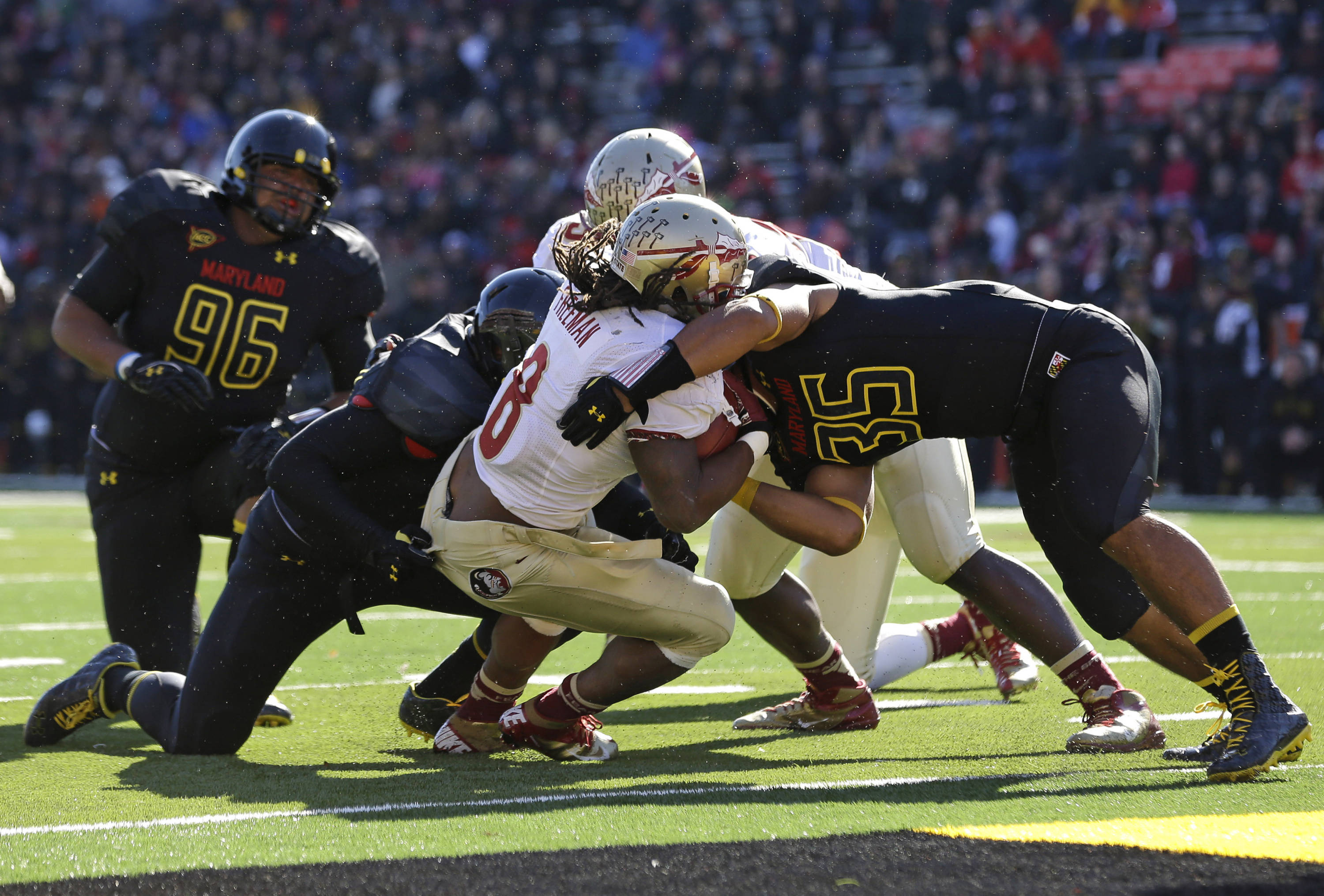 Running back Devonta Freeman, center, pushes into the end zone for a touchdown past Maryland linebacker Alex Twine (35) in the first half of an NCAA college football game in College Park, Md., Saturday, Nov. 17, 2012. (AP Photo/Patrick Semansky)